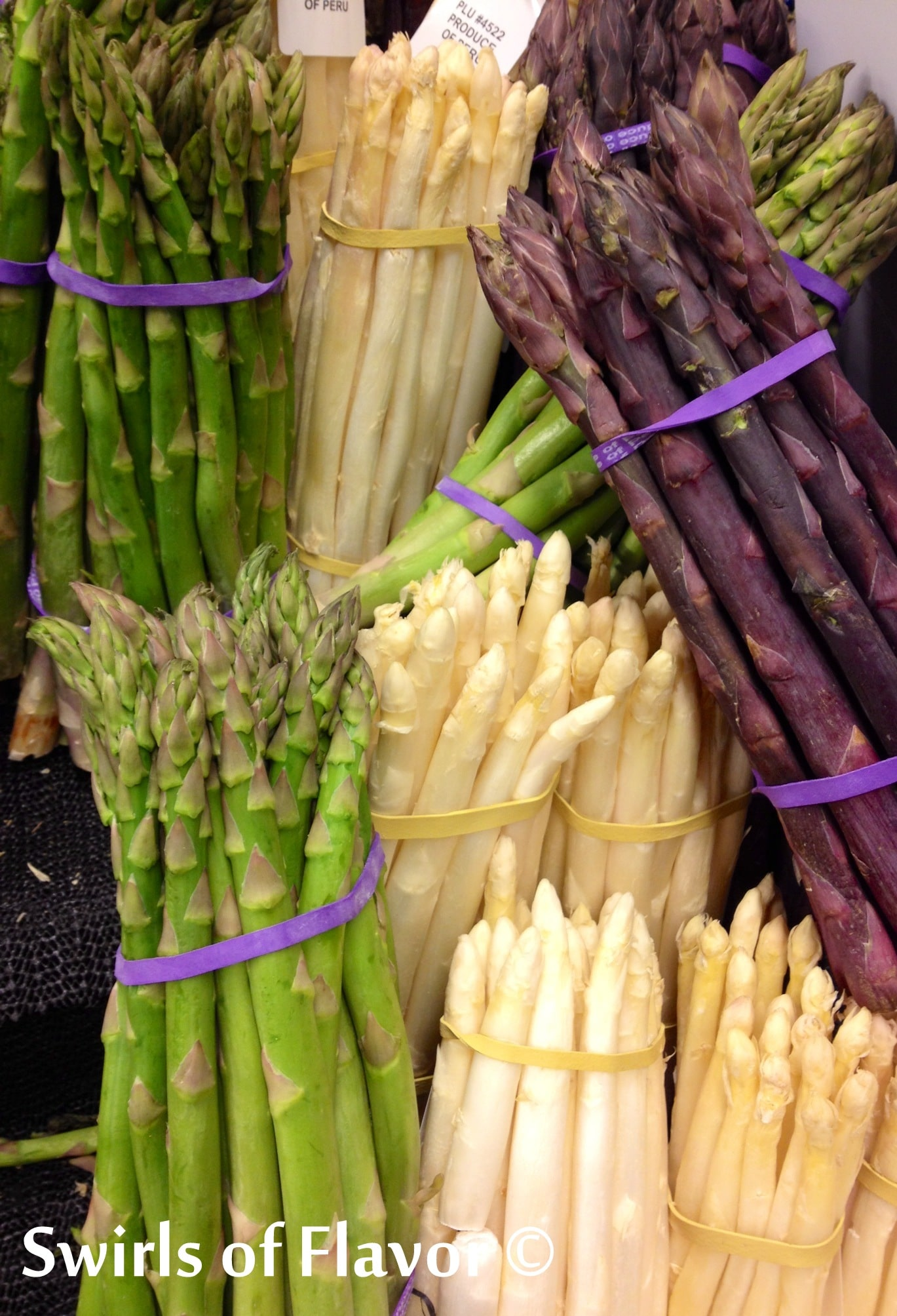 bunched of fresh asparagus in green, white and purple