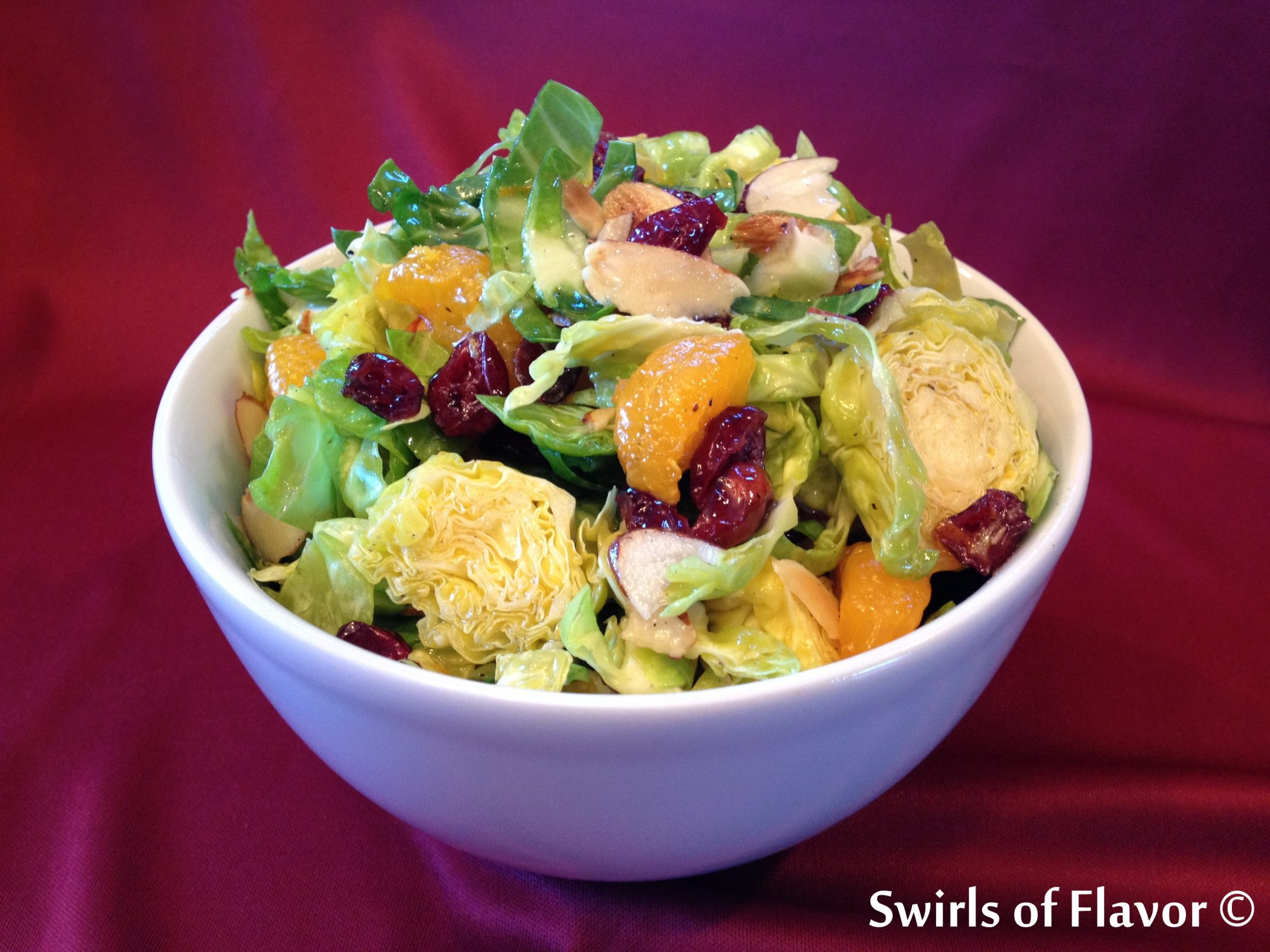 Shaved Cranberry Brussel Sprouts Salad with Orange Marmalade Vinaigrette in white bowl