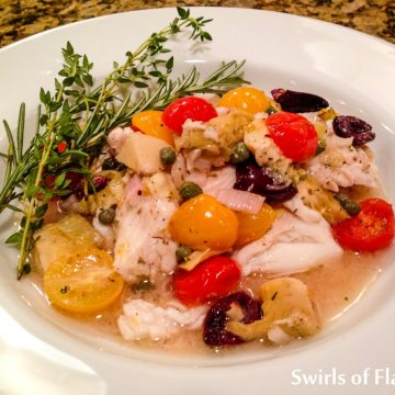 single serving of oven baked tilapia in white bowl with fresh herbs