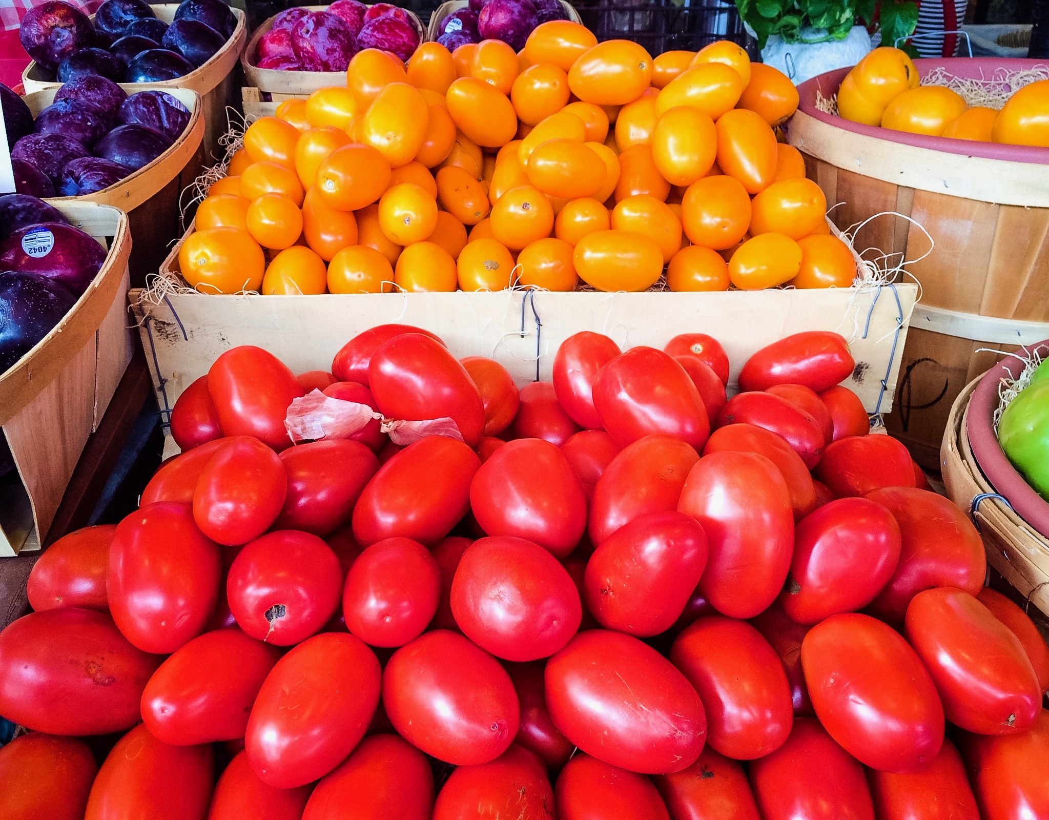 Orange and Yellow Plum Tomatoes in wooden boxes