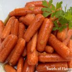 Gingered Cinnamon Honey Glazed Carrots are an easy recipe for a weeknight dinner or entertaining. Carrots are simmered in honey with a hint of cinnamon and crystallized ginger for a side dish you'll want to make over and over again! #carrots #honey #easyrecipe #sidedish #vegetable #entertaining #holiday #babycarrots #ginger #honey #recipe #swirlsofflavor