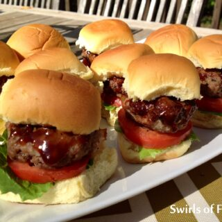 Bourbon flavored barbecue sauce glazes over these bacon studded sliders so every bite is filled with intense flavors and juiciness. bacon | bourbon | sliders | barbecue | beef | ground beef | grilling