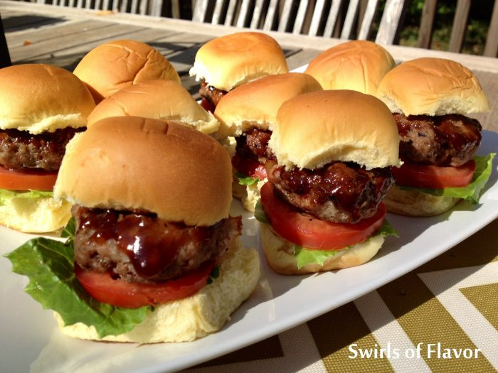 Bourbon Glazed Bacon Sliders have bits of bacon in the burger. Barbecue sauce with bourbon glazes over on the sliders making every bite flavorful and saucy. Our homemade beef burger sliders with bacon can be grilled or cooked stove top and will be the hit of every get together! #beef #beefburgers #bacon #baconburgers #bourbon #bourbonglaze #sliders #baconsliders #partyfood #gamedayfood #grilling #swirlsofflavor