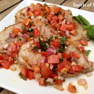 Bruschetta Pork Chops is an easy dinner recipe for sauteed pork chops with a buttery tomato and garlic topping swirled with a touch of balsamic vinegar and fresh basil.
