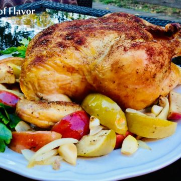 roasted chicken with apples and onions on a white platter