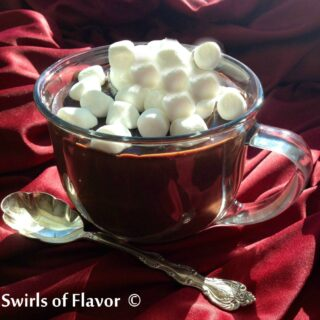 hot chocolate in a clear mug topped with mini marshmallows