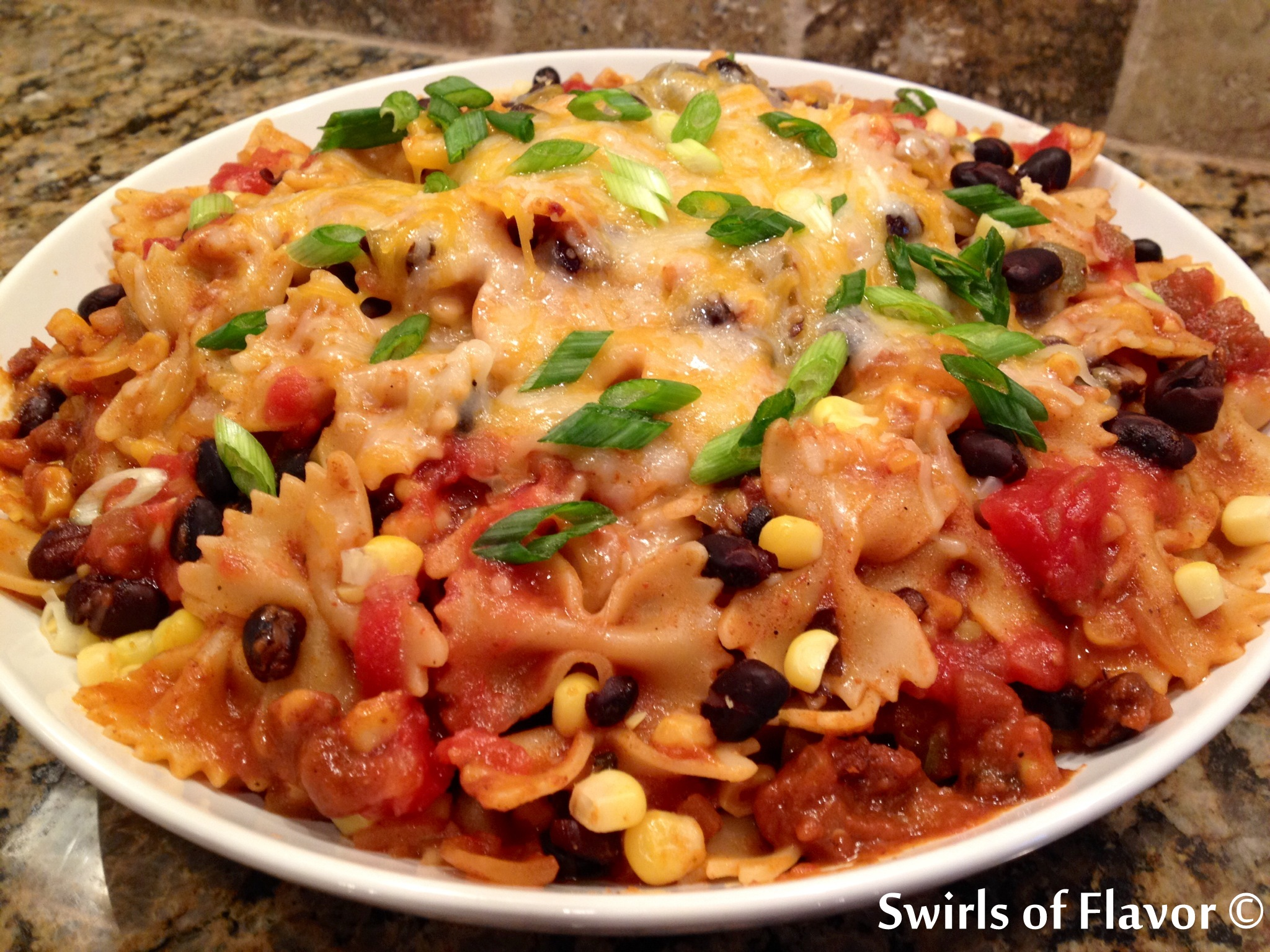 One Pot Mexicali Bowtie Pasta, an easy weeknight recipe that cooks in just minutes in one pot, is bursting with corn, black beans, pasta and cheesiness! recipe | easy | dinner | one pot | pasta | corn | black beans | mexican | #swirlsofflavor
