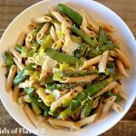 Penne and spring vegetables in a white bowl