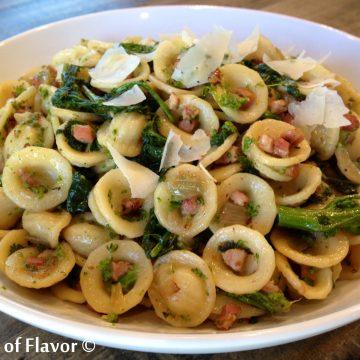 Precchiette pasta with broccoli rabe and pancetta in a white bowl
