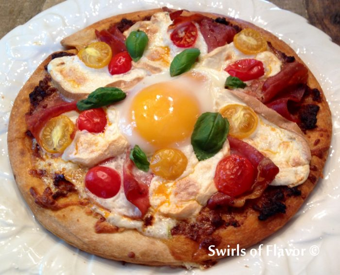 Smoked Mozzarella & Prosciutto Breakfast Pizzas are made with store bought pizza crusts topped with pesto, prosciutto, smoked mozzarella and tomatoes, then with an egg. and baked in the oven!