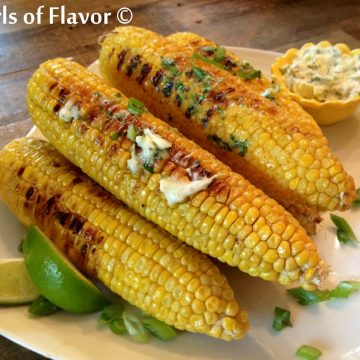 Grilled corn on the cob on platter with cilantro lime butter and lime wedges