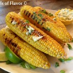 A pile of grilled corn on the cob with cilantro lime butter
