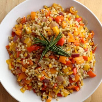 israeli couscous and sweet peppers with fresh rosemary in white dish