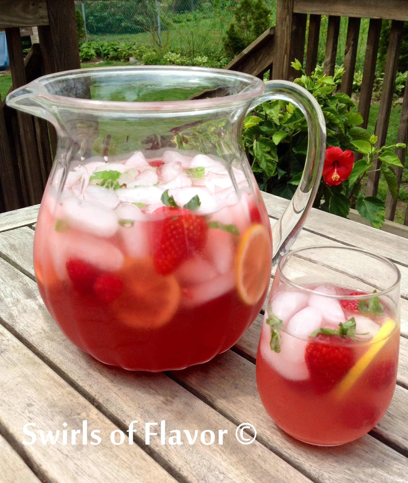 Prosecco punch with berries and lemon slices in pitcher and stemless wine glass