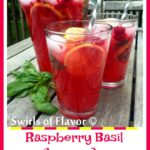 Raspberry Basil Lemonade in two glasses with straws and a pitcher