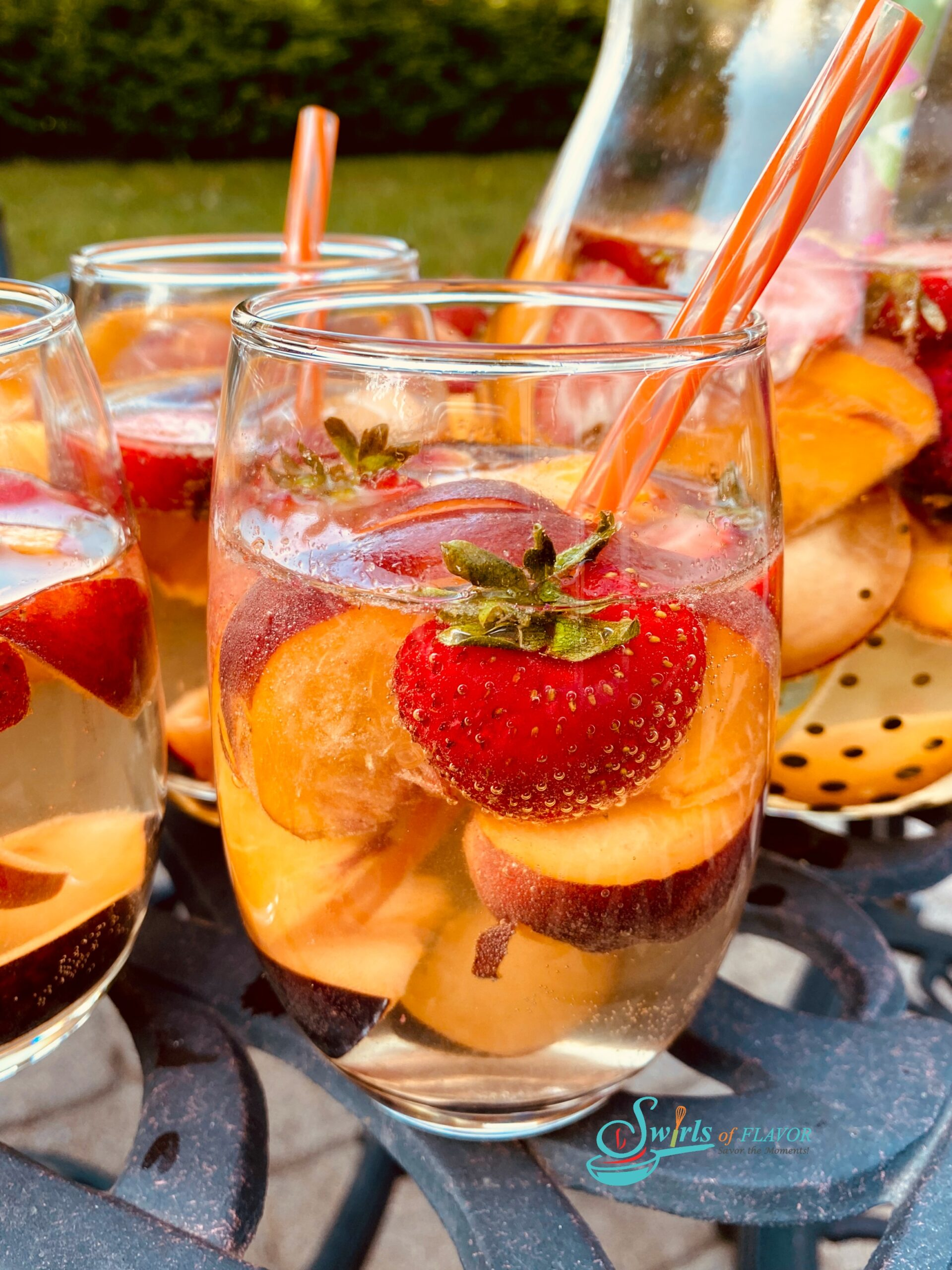 stemless wine glasses filled with peach sangria and fresh fruit