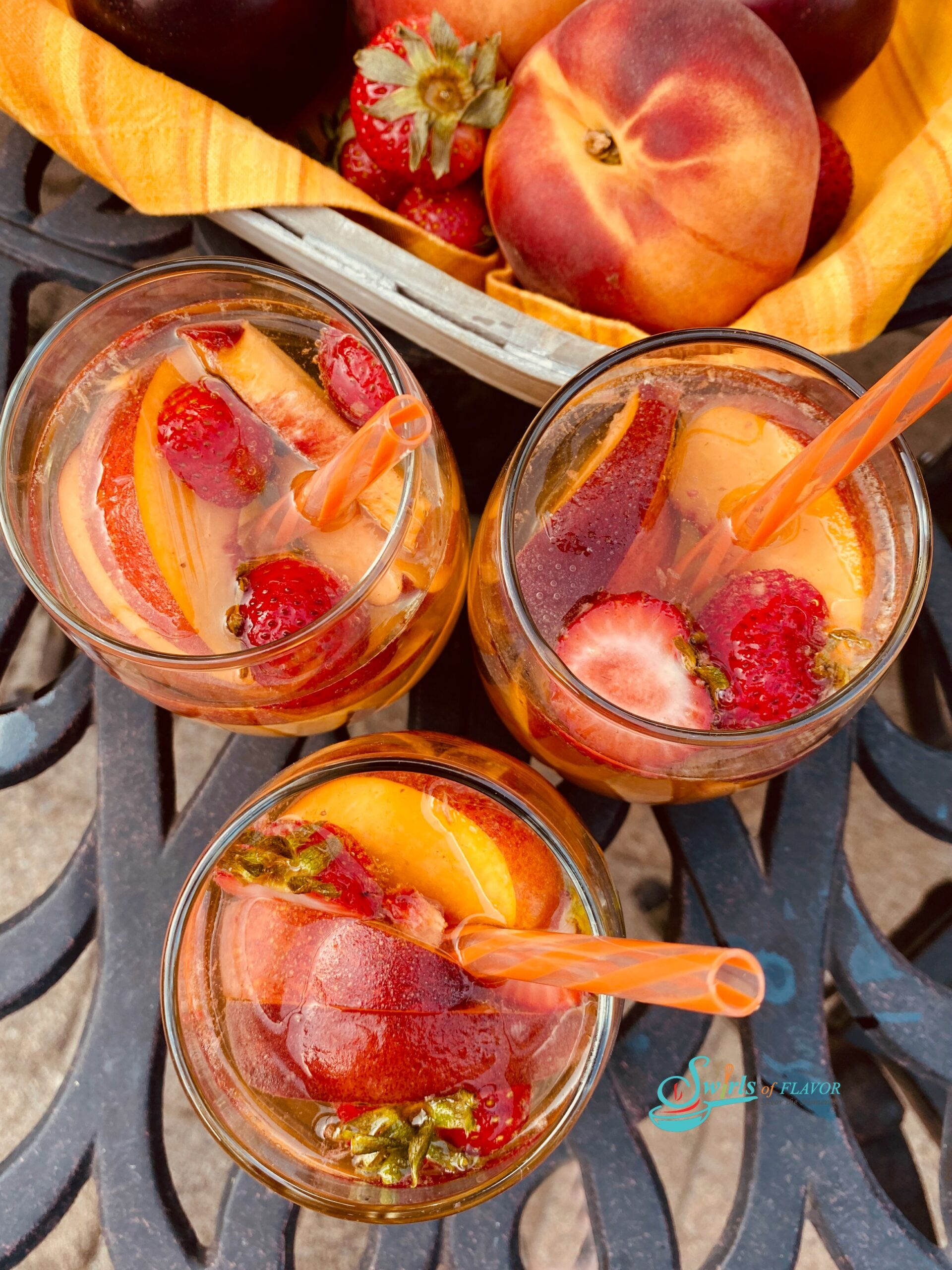 overhead photo of glasses of peach sangria and fresh fruit