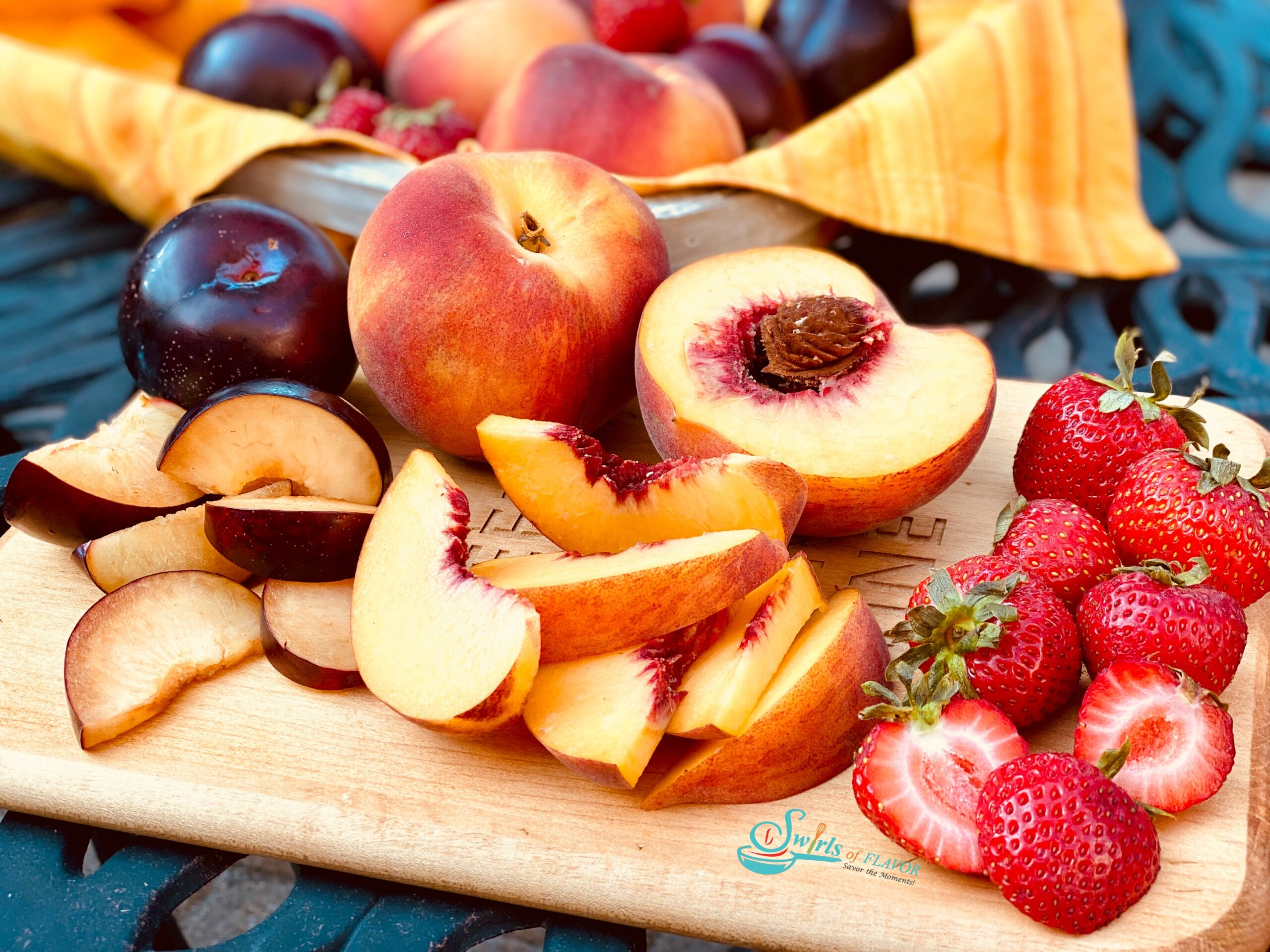 Sliced peaches, plums and strawberries on a wooden board