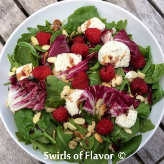Raspberry Almond Mixed Greens with Raspberry Balsamic Vinaigrette is a blend of lettuces, toasted almonds and plump raspberries tossed in a balsamic vinaigrette sweetened with a hint of raspberry jam.