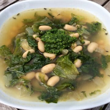 escarole soup with white beans in white bowl