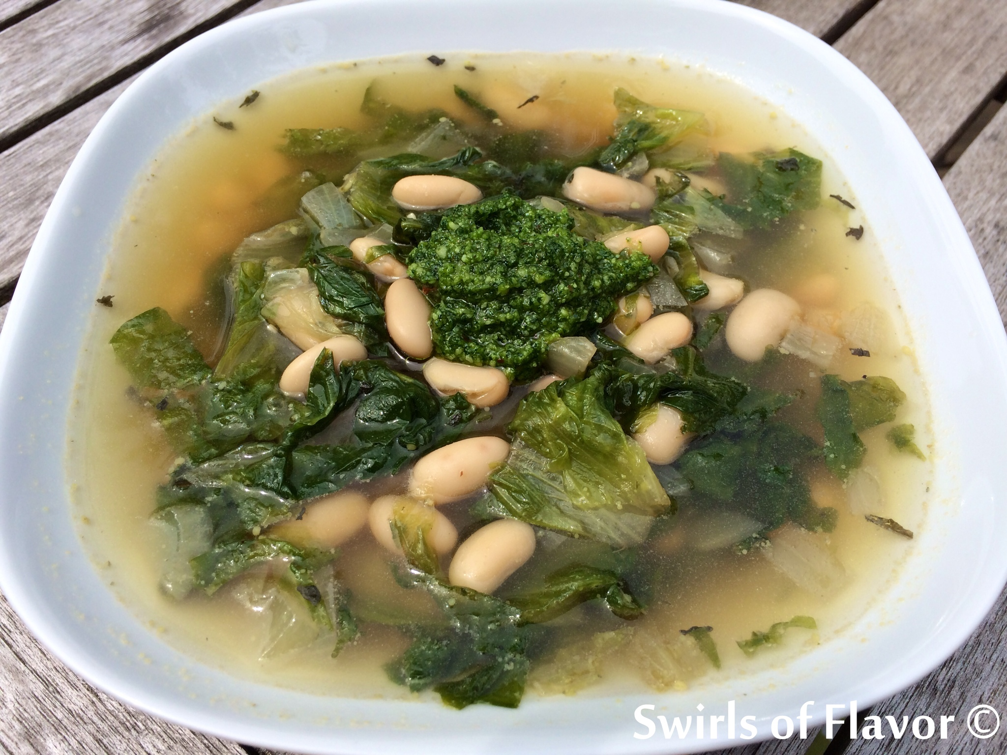 White Bean and Escarole Soup is a hearty vegetarian soup that's bursting with the flavors of fresh escarole, pesto and white beans. White Bean and Escarole Soup is a versatile recipe that can be either vegetarian, when prepared as is, or can be turned into a hearty chicken soup when replacing vegetable broth with chicken broth and adding shredded rotisserie chicken! #homemade #homemadesoup #fromscratchrecipe #easyrecipe #meatlessMonday #vegetarian #escarole #whitebeans #swirlsofflavor