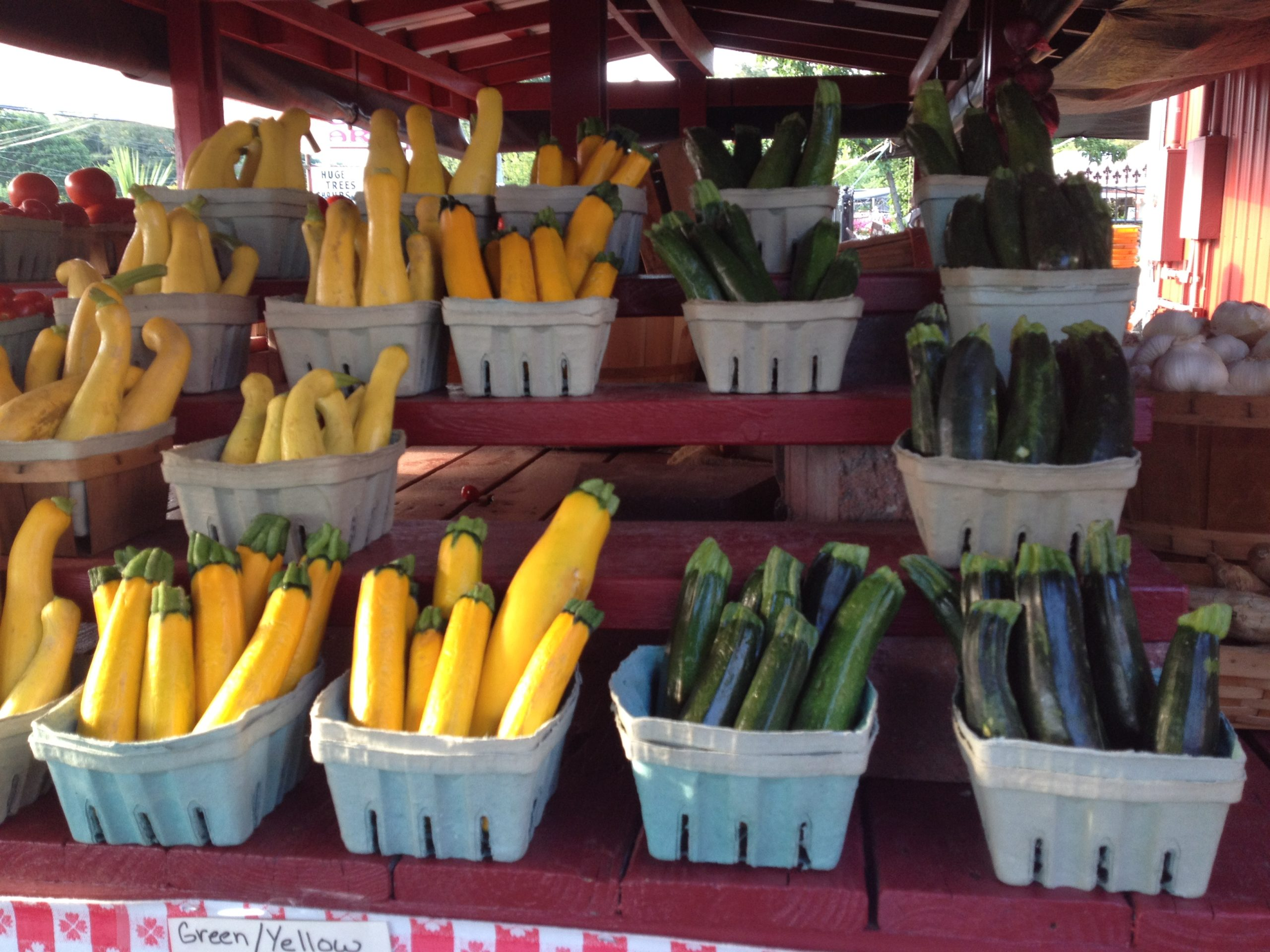 yellow squash and zucchini in baskets at a farmstand