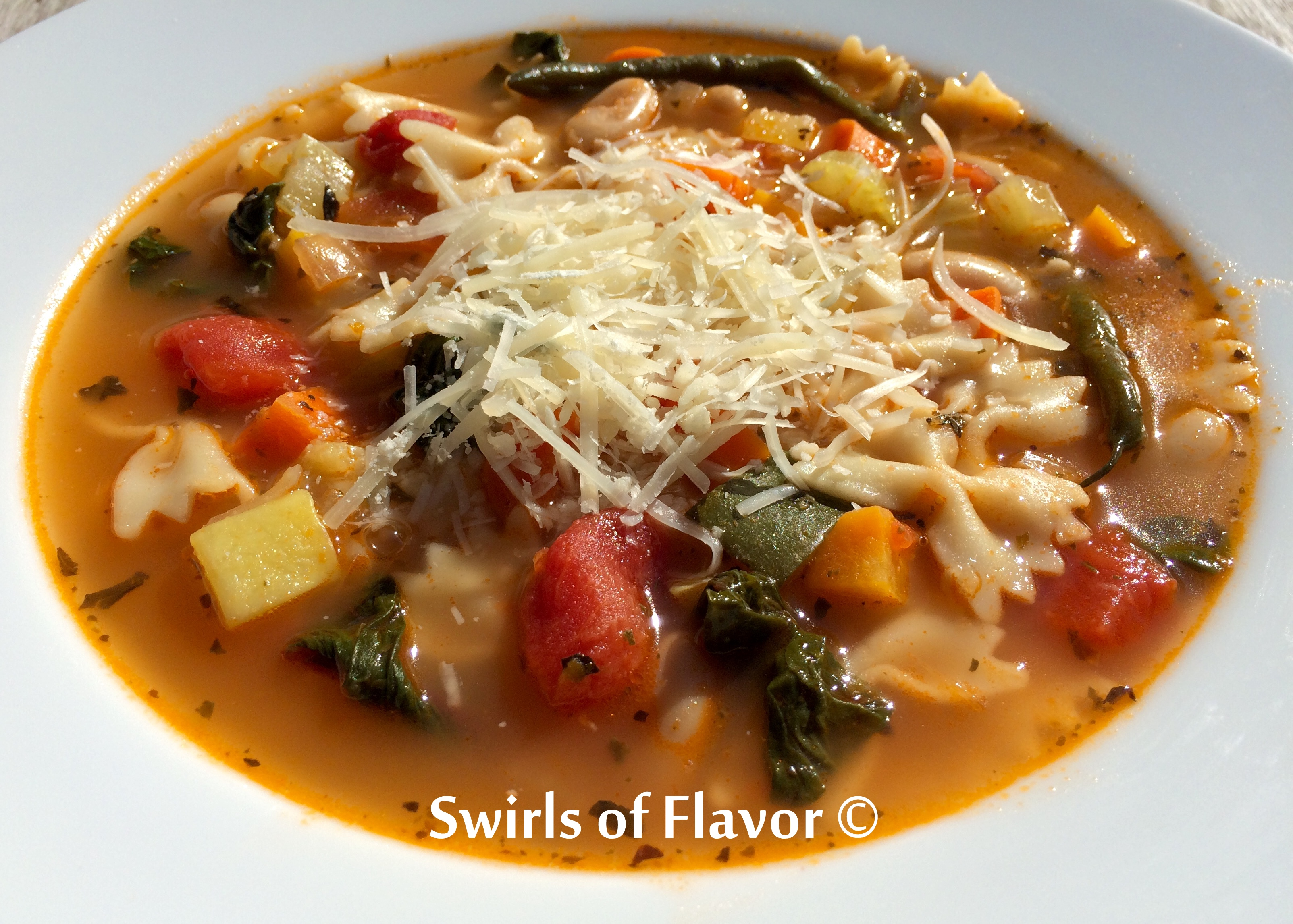 Pesto Minestrone Soup Recipe in a bowl with shredded Parmesan cheese