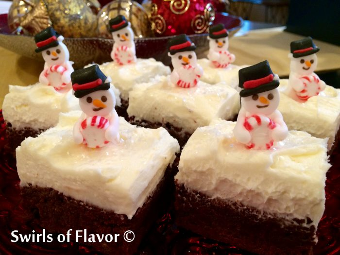Homemade fudgy brownies are topped with a peppermint buttercream frosting and royal icing snowmen for a festive holiday dessert!