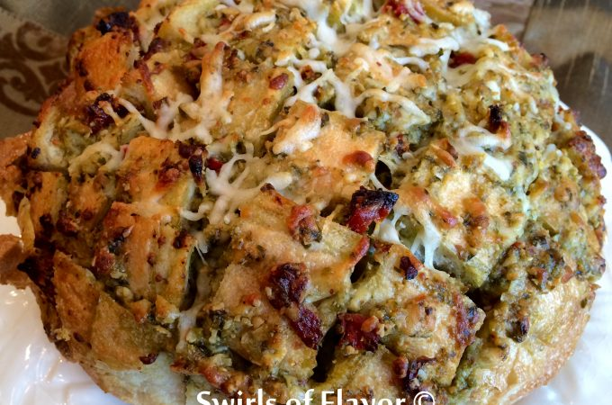 Cheesy Pesto Pull-Apart Bread is an easy appetizer recipe made with just four ingredients. The perfect blend of pesto, mozzarella and sundried tomatoes fill every nook and cranny of this baked pull apart bread! A perfect appetizer recipe for the holidays! #bread #appetizer #holiday #entertaining #pesto #pullapartbread #swirlsofflavor