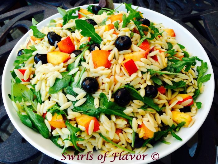 Blueberry Peach Orzo is an easy seasonal recipe filled with lime-kissed orzo pasta and studded with fresh juicy peaches and succulent blueberries. Tender peppery arugula leaves offset the fruity sweetness creating aperfect balance of flavors.side dish | fresh fruit | pasta | orzo | blueberries | peaches | easy recipe | arugula | farmers market | #swirlsofflavor