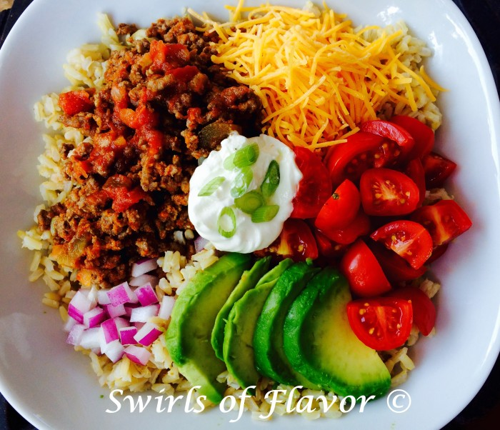 Brown Rice Taco Bowl is filled with seasoned beef and salsa, creamy avocado, juicy tomatoes, cheddar cheese and red onion over good-for-you brown rice. All the flavors of a taco in a bowl! #tacos #tacotuesday #brownrice #tacobowl #avocado #dinner #easyrecipe #notortillataco #swirlsofflavorr