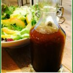Cruet of honey orange balsamic vinaigrette with salad in background