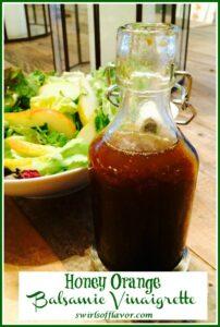 Cruet of honey orange balsamic vinaigrette with salad in background