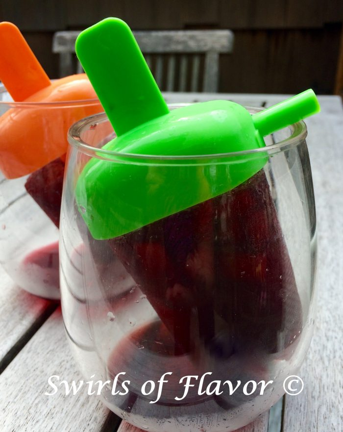 Pinot Noir, pomegranate juice and a fresh plum are all frozen to perfection in this easy recipe for Pomegranate Plum Wine Ice Pops! For the little kid in every grown up! #easyrecipe #frozen #icepop #wineicepop #dessert #frozendessert #summer #drinks #cocktail #PinotNoir #swirlsofflavor