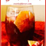 stemless wine glass with pomegranate punch and orange with text overlay