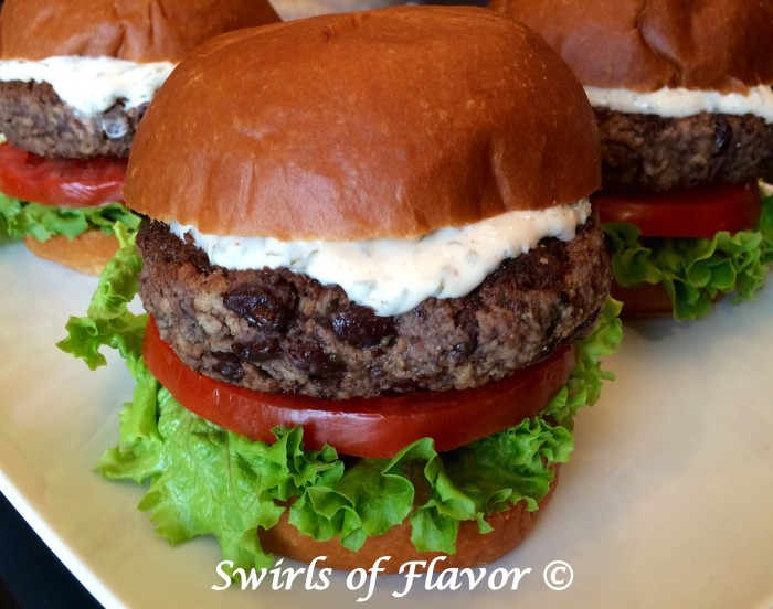 Black bean burgers are perfectly seasoned with chili powder and cumin and topped with a creamy sauce that's bursting with the fresh flavors of cilantro and lime. Meatless Monday never tasted so good! burgers | black beans | black bean burgers | meatless | vegetarian