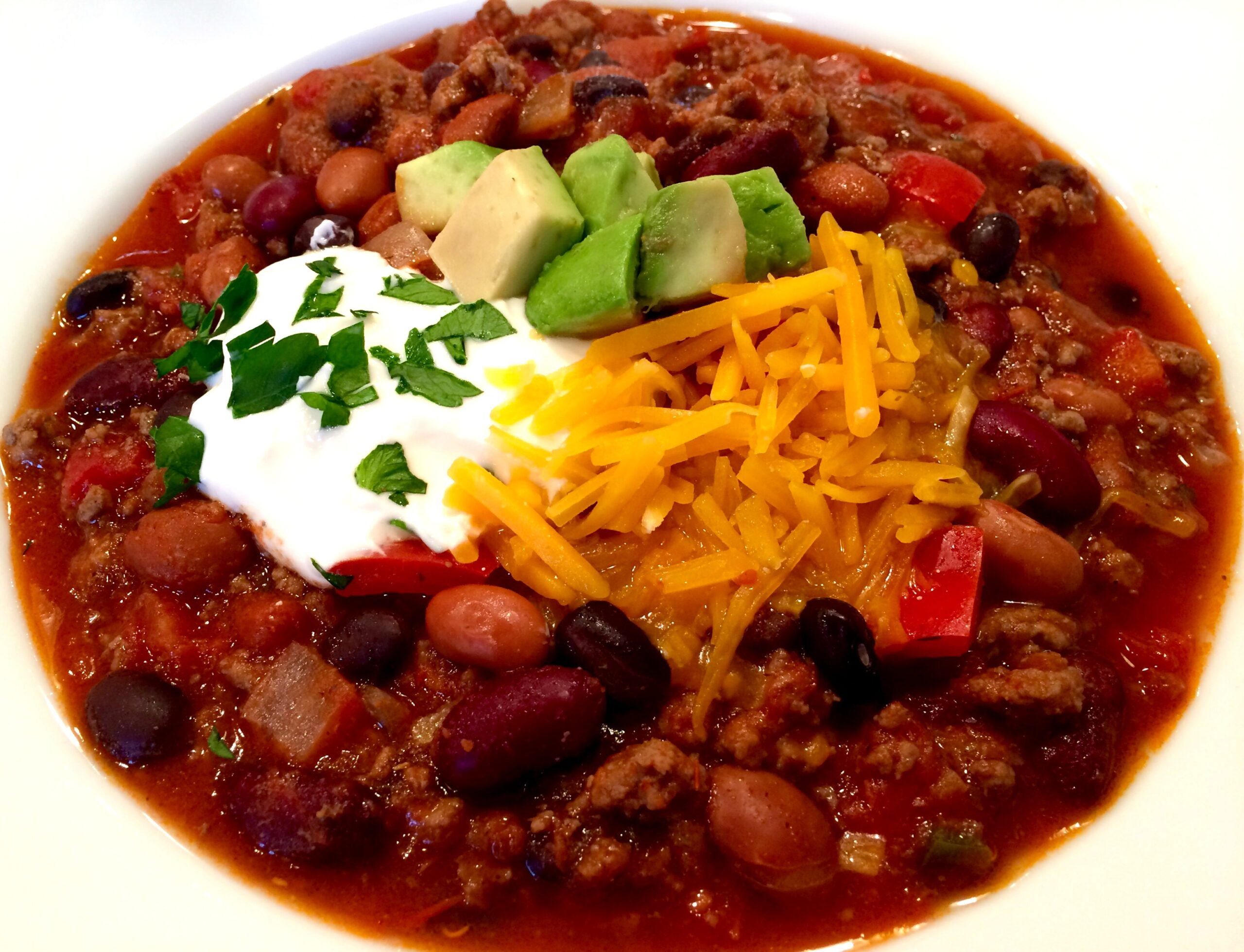 bowl of been and ground beef chili with toppings