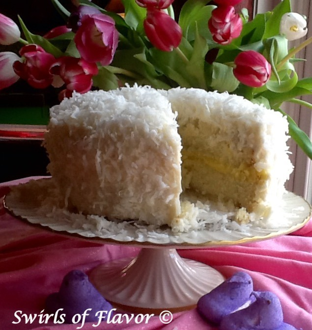 coconut lemon cake on cake stand with slice out