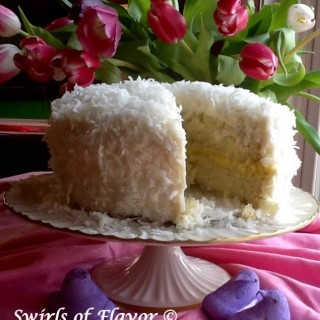 You'll love Coconut Lemon Layer Cake for your holiday or springtime dessert. Layers of coconut cake topped with coconut buttercream frosting and flaked coconut surround a tangy lemon filling making every bite a little taste of heaven! cake | recipe | coconut | lemon | dessert | easy | holiday
