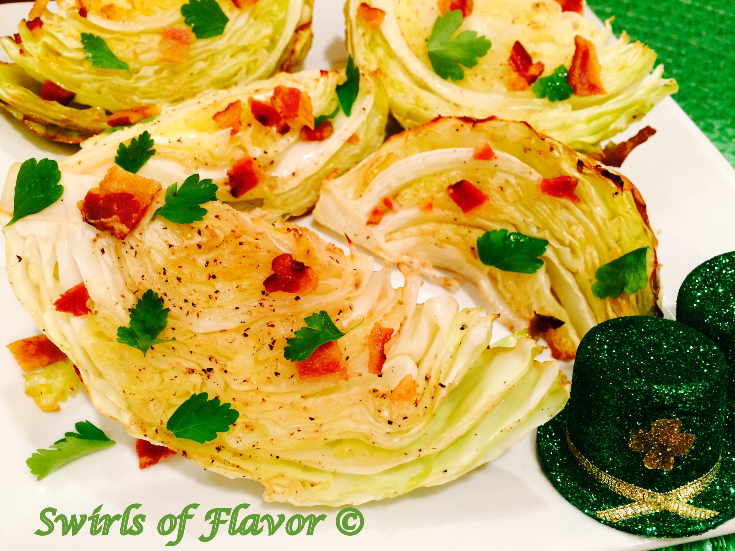 baked cabbage wedges with bacon and parsley on a white dish
