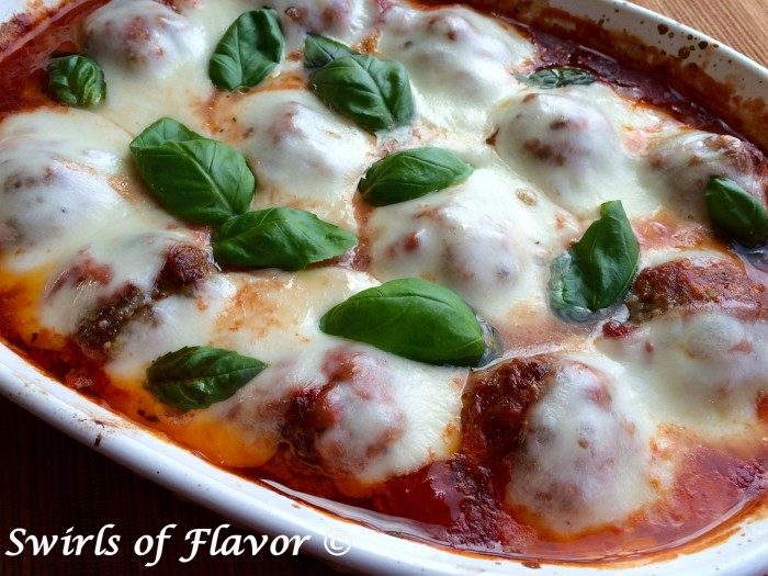 Baked Meatballs Parmesan, an easy homemade meatball recipe that's cheesy and saucy, will warm you up for dinner tonight! Just shape our homemade beef mixture into meatballs, smother with sauce and let them bake themselves in the oven. #meatballs #homemademeatballs #meatballsparmesan #easyrecipe #dinner #ovenbakedmeatballs #casserole #swirlsofflavor