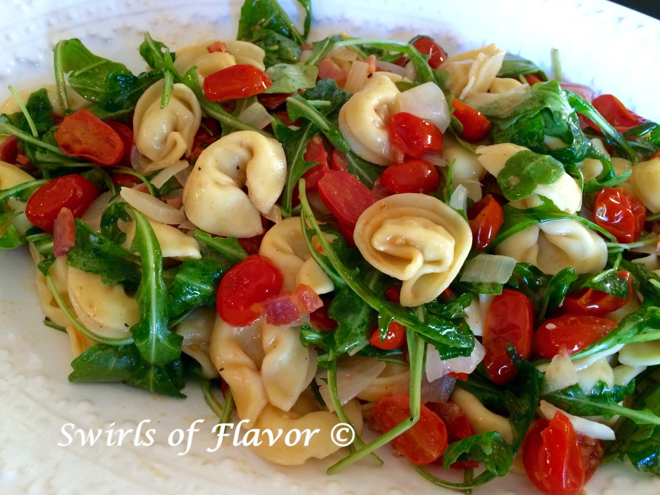 Tortellini with arugula and tomatoes on a white platter