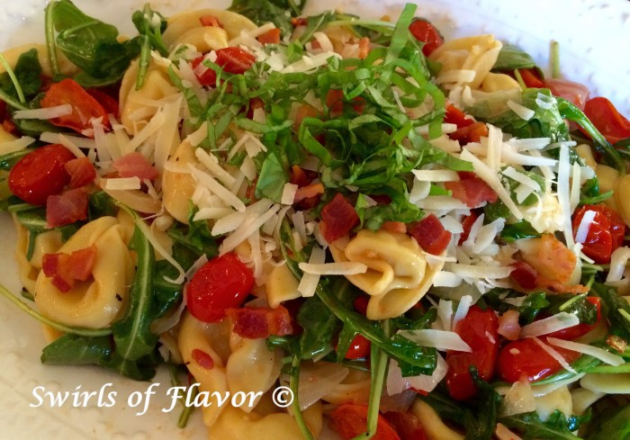 Tortellini with tomatoes and thinly sliced fresh basil on top
