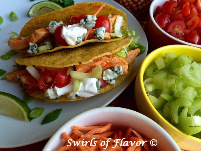 Tacos and buffalo chicken combine to make Buffalo Chicken Tacos! Tortillas are filled with a saucy spicy buffalo chicken topped with celery, carrots, tomatoes and creamy Roquefort blue cheese and combine two favorite foods! An easy recipe for your Taco Tuesday dinner! #tacos #buffalochicken #chicken #TacoTuesday #easyrecipe #familyfavorite #weeknightdinner #swirlsofflavor