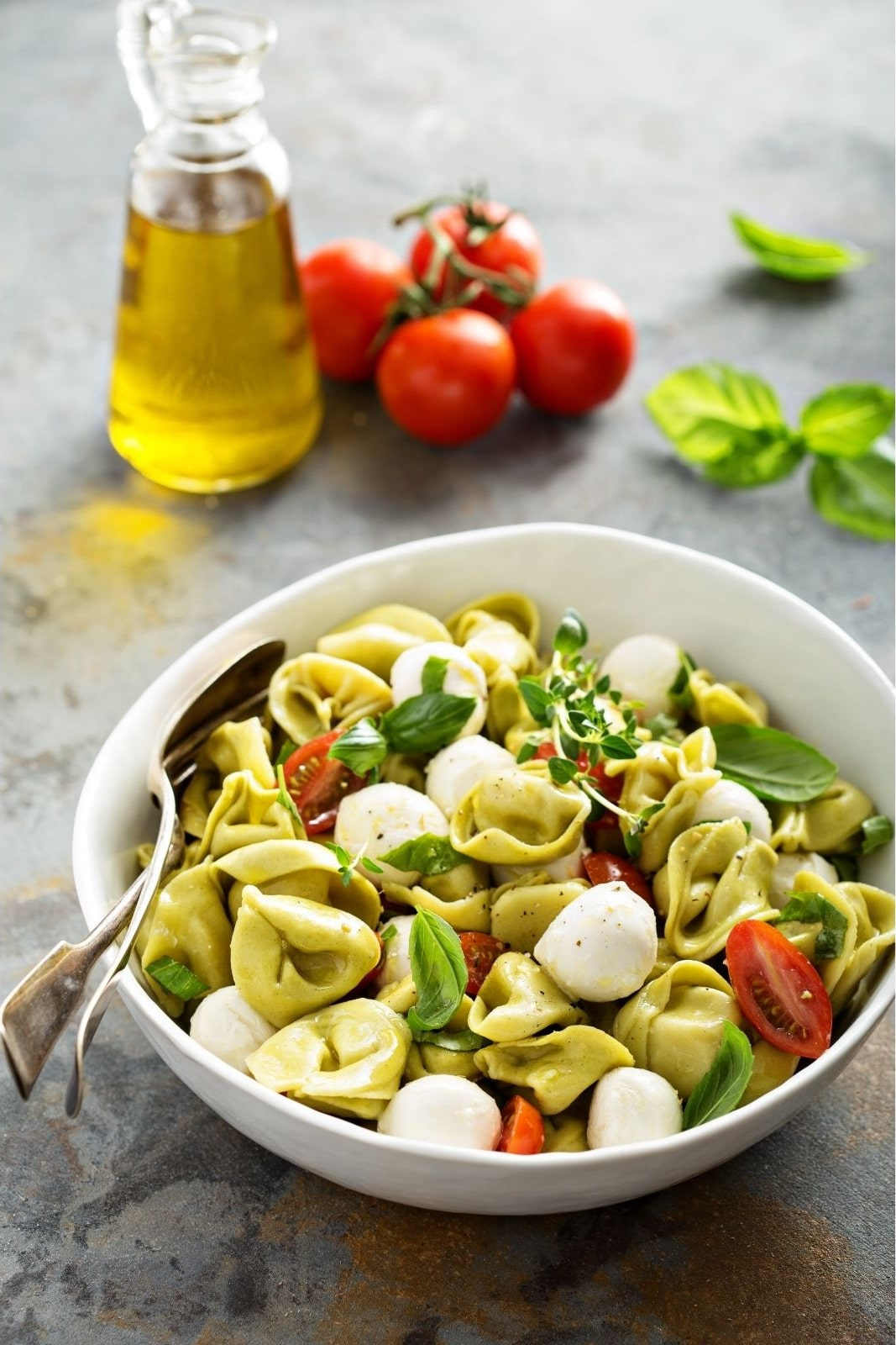 pasta salad with totellini in white bol with olive oil cruet and fresh tomatoes