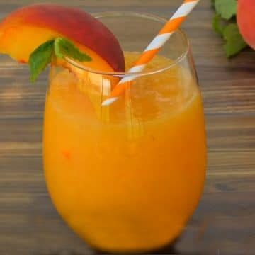stemless wine glass of frozen peach Bellini Recipe with peach and mint garnish
