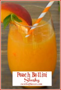 Peach bellini slushy in a stemless wine glass with peach slice and mint and a straw