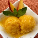 Two scoops of mango sorbet with mango slices and fresh mint in white dish