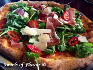 Grilled Prosciutto Parmesan & Arugula Pizza is topped with a bed of baby arugula greens lightly tossed in a white balsamic vinaigrette dressing. Baby arugula, tomatoes and prosciutto combine to make each bite the perfect combination of summer flavors.