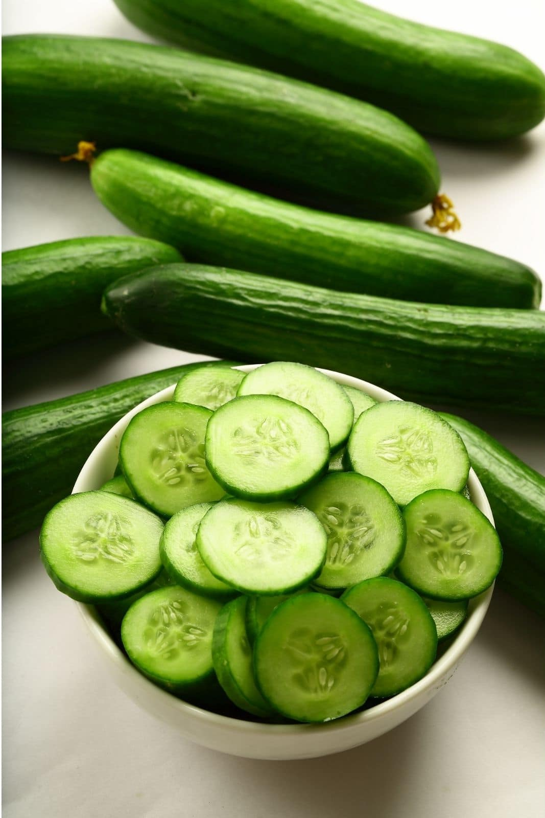 sliced cucumbers in a bowl with whole cucumbers